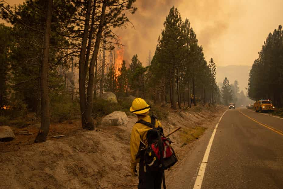 A firefighter watches as the Caldor fire approaches in Meyers, south of South Lake Tahoe.The Caldor fire has scorched nearly 312 sq miles since breaking out on 14 August.