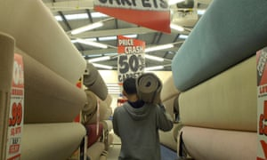 A man carries a roll of carpet in a Carpetright store