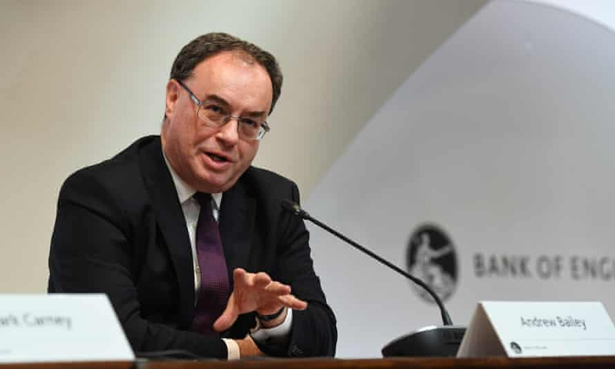 Andrew Bailey sitting at a Bank of England press event, speaking and gesturing with one hand