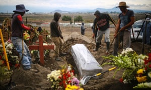 Workers of the San Miguel Xico cementery bury a coffin of a presumed Covid-19 victim on 24 June 2020 in Valle de Chalco, Mexico.