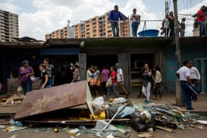 Residents in Caracas inspect the damage after violence and looting.