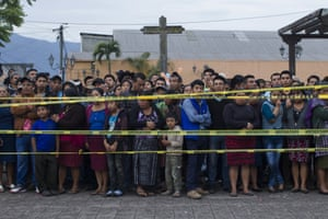 Neighbours stand outside a temporary morgue in Alotenango