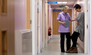 Nurse comforts young person in hospital corridor