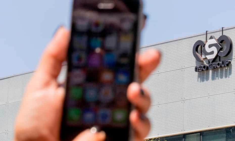 An Israeli woman uses her iPhone in front of the building housing the Israeli NSO group, in Herzliya, near Tel Aviv.