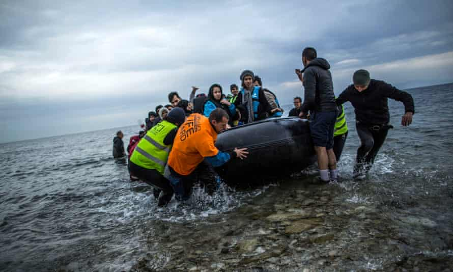 Refugees and migrants are helped by volunteers as they arrive in Lesbos in Greece