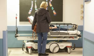 A patient waiting on a trolley in a corridor in A&E.