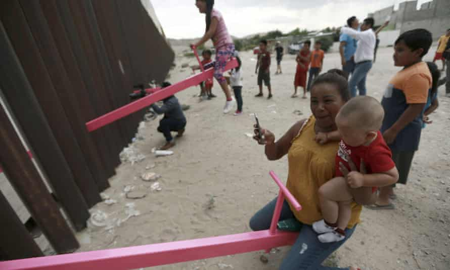 A mother and her baby play on a seesaw installed between the steel fence that divides Mexico from the United States in Ciudad de Juarez, Mexico in 2019.