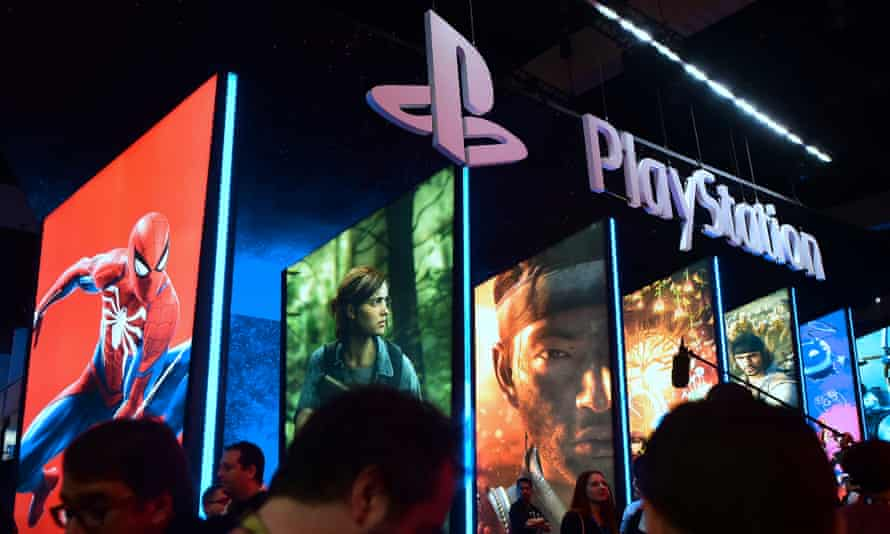Visitors wander in front of the Playstation posters at the 2018 E3 expo