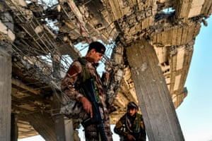 Members of the SDF check a building near the stadium as they clear the last positions