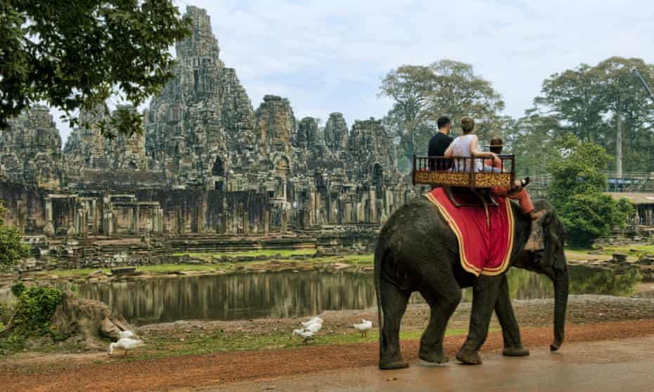 Tourists take a guided elephant ride to an ancient temple in Siem Reap, Cambodia.