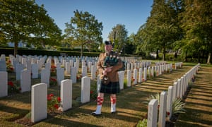 Jérôme Levannier plays Amazing Grace in Ranville cemetary as he walks amongst the graves of soldiers killed during the battle for Normandy.