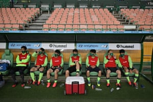 Jeonbuk Motors' players sit in the dugout prior to the opening game of South Korea's K-League.
