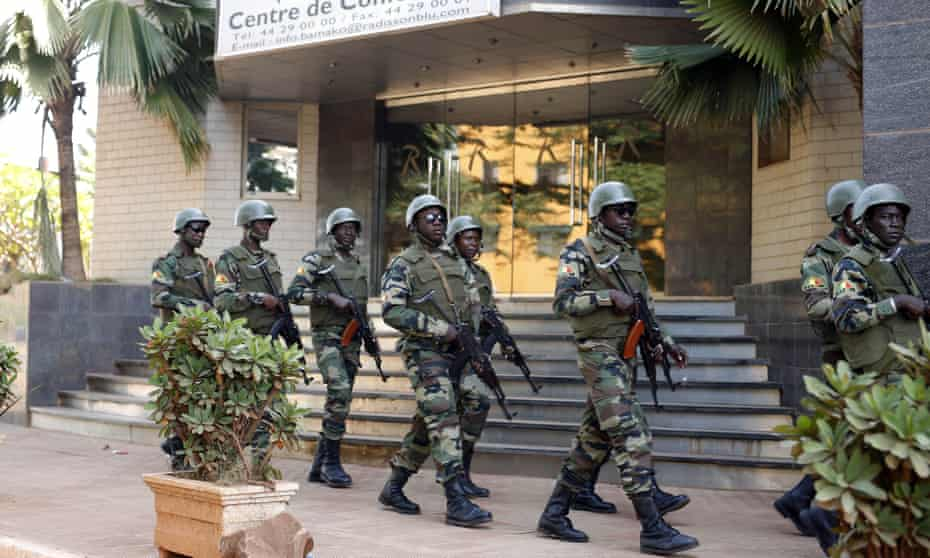 Soldiers patrol outside the hotel in Bamako that was attacked by Islamic extremists.