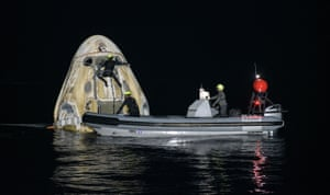 Support teams work around the SpaceX Crew Dragon spacecraft shortly after it had landed in the Gulf of Mexico off the coast of Panama City.