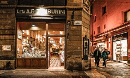 At night, two shoppers walk past Tamburini, Antica Salsamenteria Bolognese, Bologna, Italy.