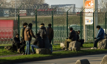 Migrants gather near a barbed wire fence at a truck parking lot in Calais