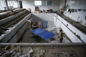 Ukrainian soldiers play table tennis in a damaged swimming pool in the village of Marinka