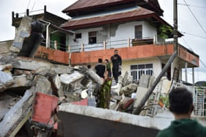 Rescuers search for survivors among the ruin of a building damaged by an earthquake in Mamuju