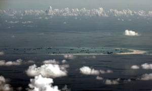 An aerial file photo taken though a glass window of a Philippine military plane shows ongoing land reclamation by China on Mischief Reef in the Spratly Islands in May 2015.