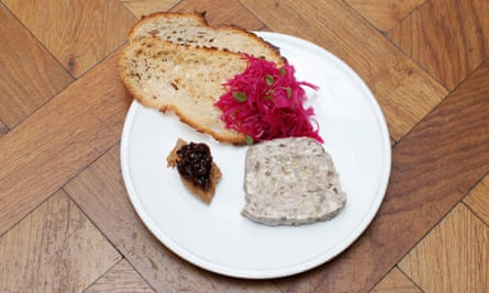 A slice of pork terrine, two slices of toast with red cabbage at one end, and a pile of prune mustard paste