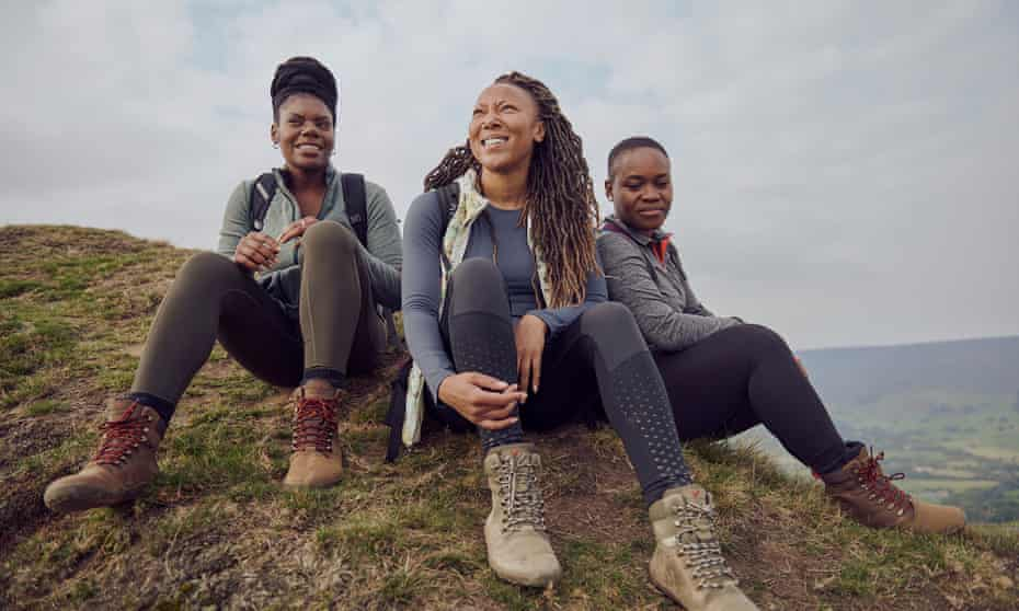 Rhiane Fatinikun (centre of three women hikers), founder of Black Girls Hike on a hill in the UK while on a hike.