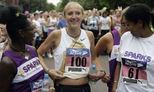 Paula Radcliffe running and smiling, holding up her T-shirt to show her belly at five months pregnant