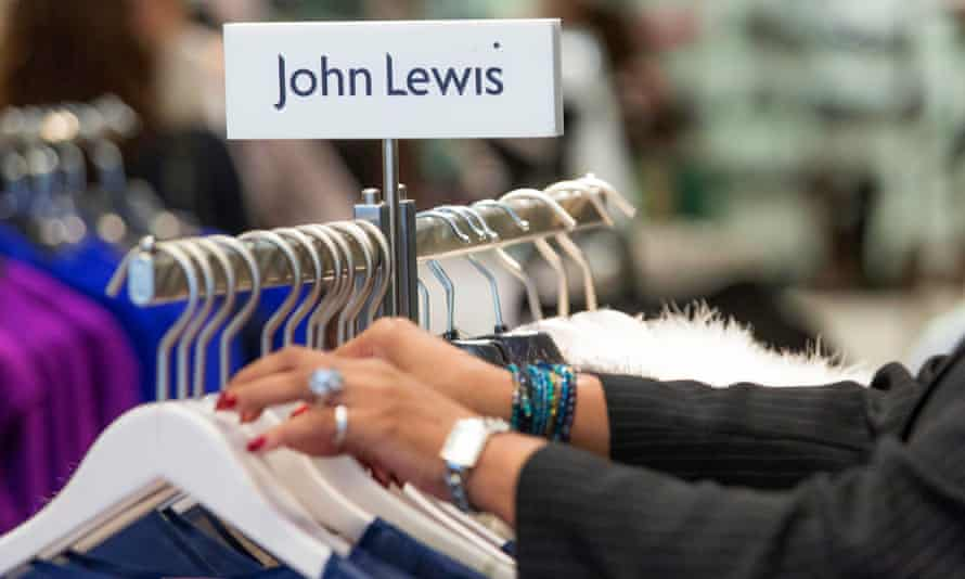 A customer browses items of clothing hanging on a rail inside a John Lewis