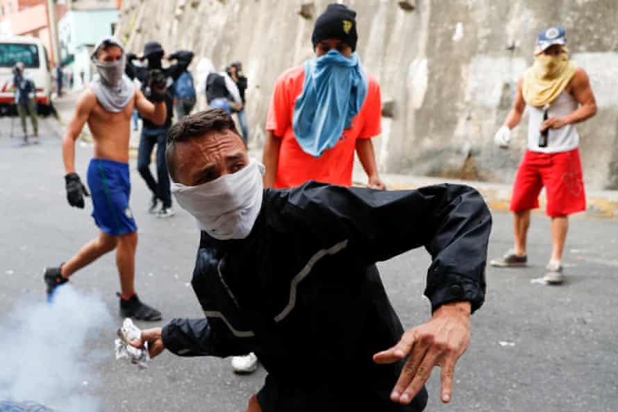 A demonstrator throws back a tear gas canister while clashing with Venezuelan National Guards during a protest close to one of their outposts in Caracas