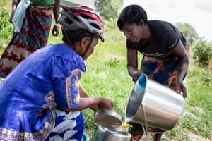 Hilda Ndoka (right) and Elizabeth Kankoyo (left) pour the milk they have collected into an urn, ready to transport by bike to the depot in Zimba.