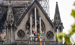 Workers shore up the charred Notre Dame facade after fire ripped through the gothic cathedral.