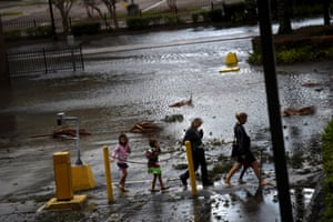 A family walks through floodwaters in Jacksonville