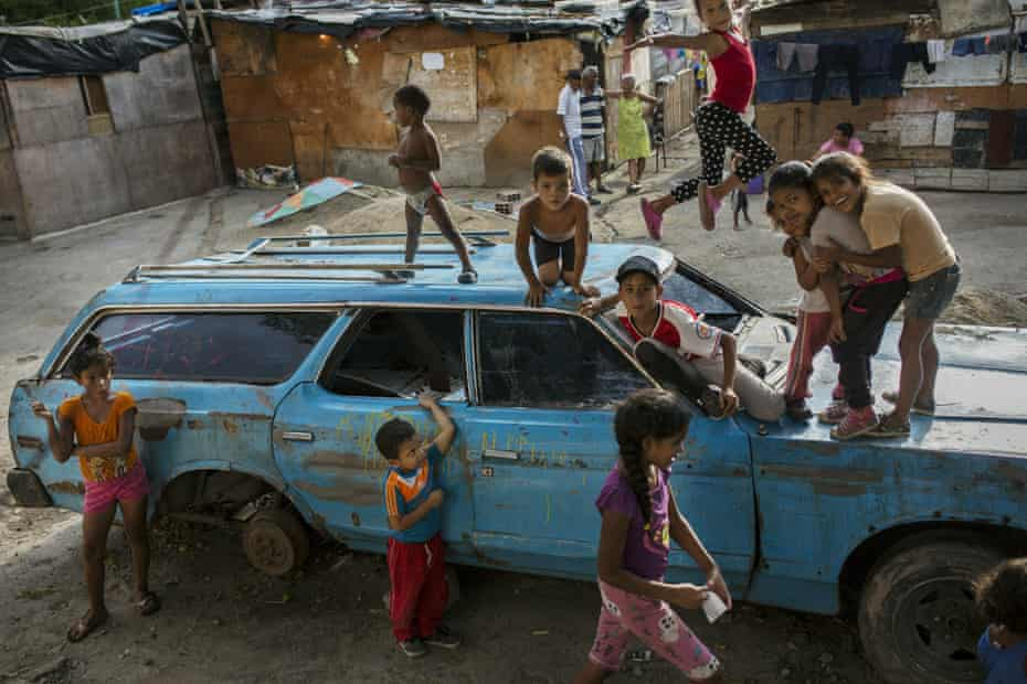Children play on top of an abandoned car at the Aguerridos Liberator shanty town in Caracas, Venezuela, 9 May