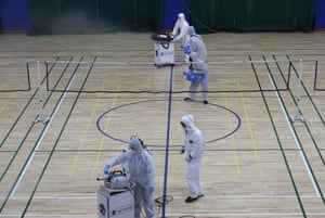 Workers in protective suits spray disinfectant at an indoor gymnasium in Seoul, South Korea