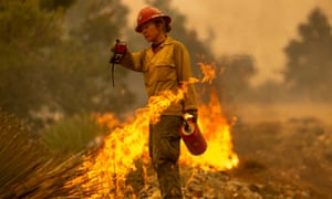 Sara Sweeney uses a drip torch to set a backfire to protect mountain communities from the Bobcat fire in the Angeles national forest.