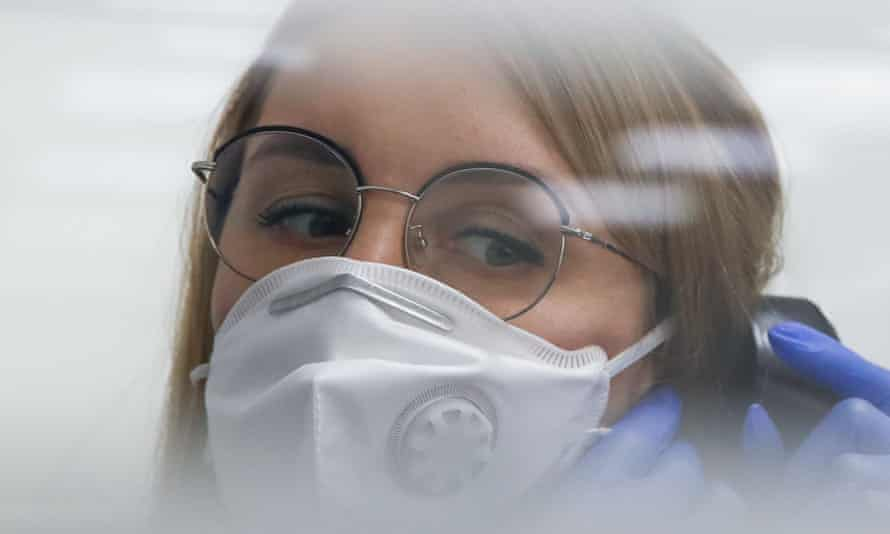 A young woman in a face mask and glasses