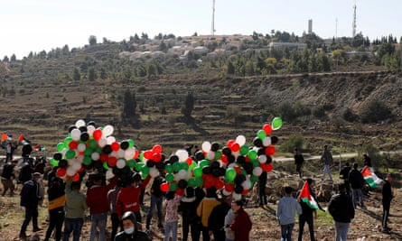 Palestinians hold balloons during a protest against Pompeo's visit, near the Israeli settlement of Psagot.