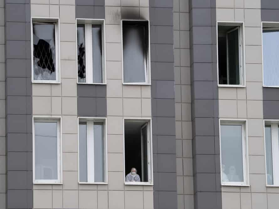 A member of the medical staff looks through a window below the scene of the fire at St George hospital.