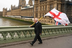 A man carries the English national flag and a union flag as he walks along Westminster Bridge by the Houses of Parliament