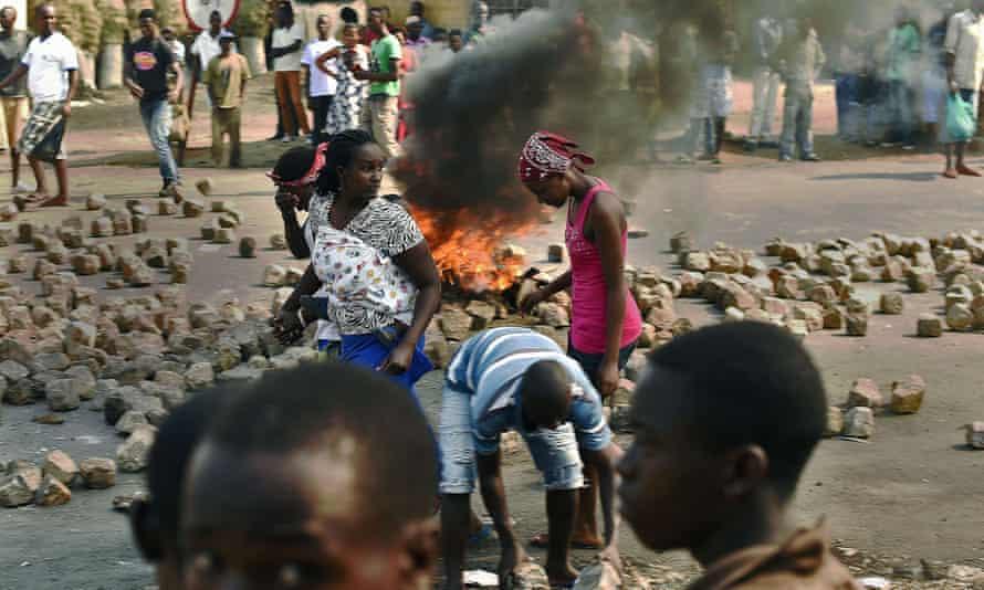 People walk past a barricade in Bujumbura, July 2015.