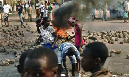 Women walk past a burning barricade in the Burundian capital, Bujumbura.