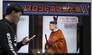 A pedestrian walks past a monitor broadcasting Emperor Akihito's abdication in Tokyo.