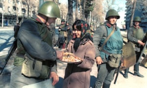 A woman offers a treat to soldiers in Dushanbe, Tajikistan, after a state of emergency was declared following an unauthorised rally in February 1990.