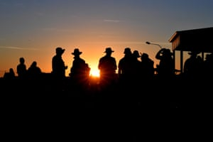 People gather outside the famous Birdsville Hotel as the sun sets in Birdsville