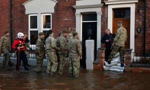 Member of the armed forces check on residents on Lismore Street, following flooding in Carlisle.
