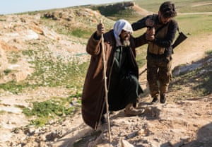 A SDF soldier helps an elderly man who fled heavy fighting in the city of Baghuz, reach a civilian collection point for suspected Isis families, on 12 February 2019