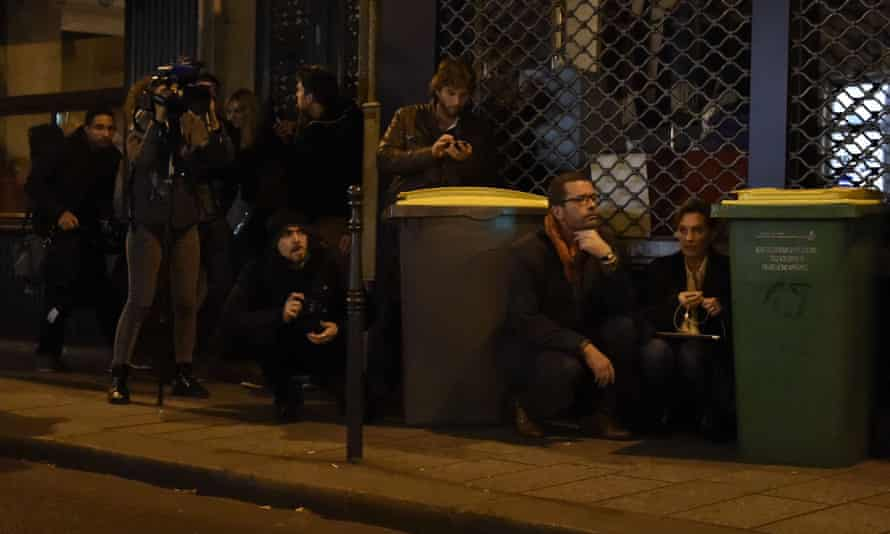 Journalists take cover near the Bataclan concert hall.