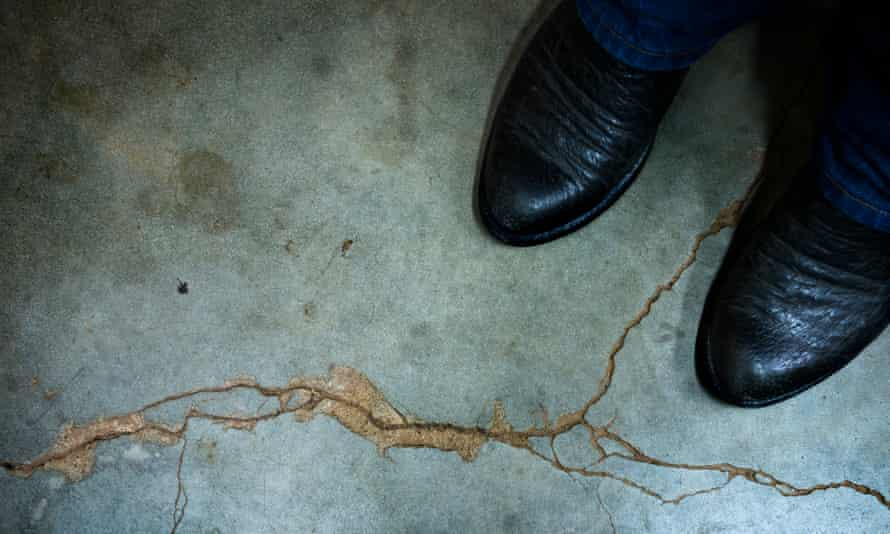 Gary Landra stands on a crack across his basement floor that he says was caused by an earthquake in Prague, Oklahoma.