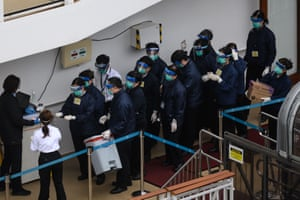 Members of the Hong Kong Department of Health wearing protective gear queue up to clean their hands on the deck of the World Dream)