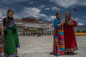 Women wear traditional style clothing as they pose for photos in the square in front of the Potala Palace