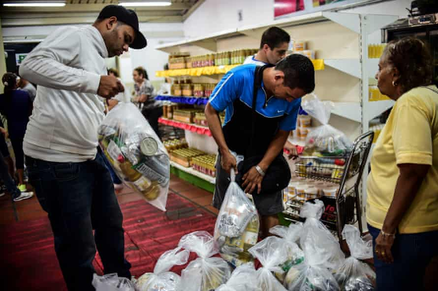 People check bags of foodstuff inside one of the food distribution centres, which have been set up by local committees 'for supply and production' in Caracas.